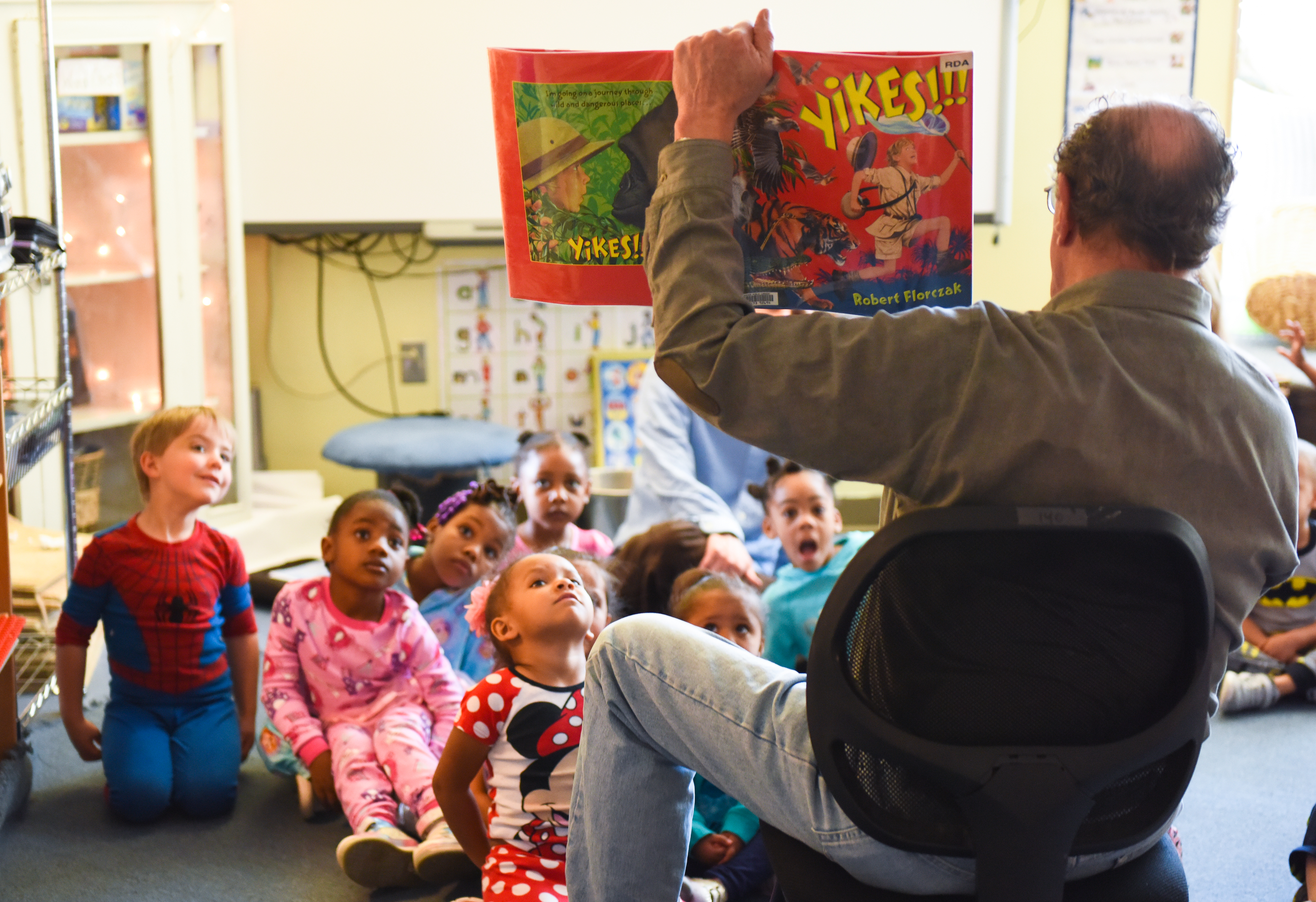 A seated man reads a picture book to a diverse group of children sitting around his feet in a child care setting.